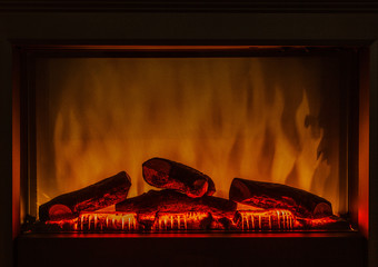 Closeup of electric artificial fireplace orange fire interior