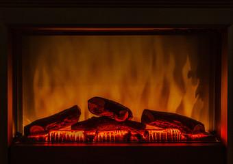 Closeup of electric artificial fireplace orange fire interior