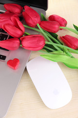 Computer with red heart and flowers on table close up