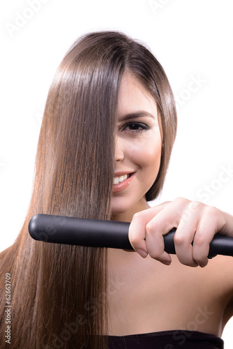 Woman doing hairstyle with hair straightener isolated on white