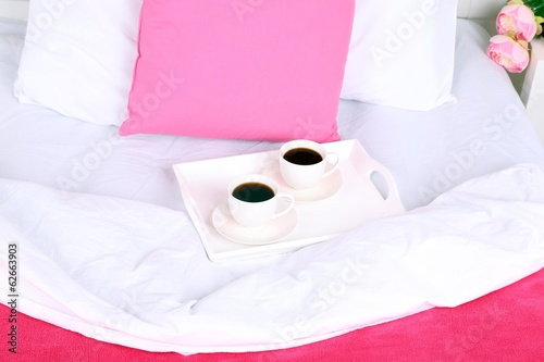 Cups of coffee on comfortable soft bed with pillows