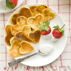 Heart shaped pancakes with fresh strawberries