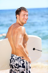 Handsome male surfer portrait on summer beach