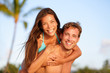 Vacation couple fun on beach, man giving piggyback