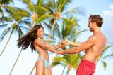 Beach couple fun on vacation dancing playful
