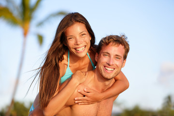 Vacation couple fun on beach, man giving piggyback