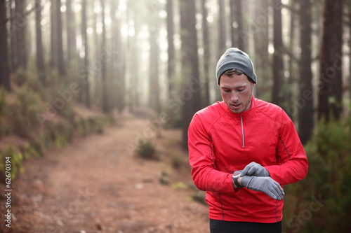 Trail runner looking at heart rate monitor watch