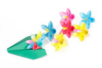 Green paper plane and many colored spring flowers