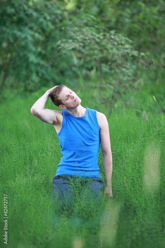 Caucasian man with eyes closed practicing yoga on meadow