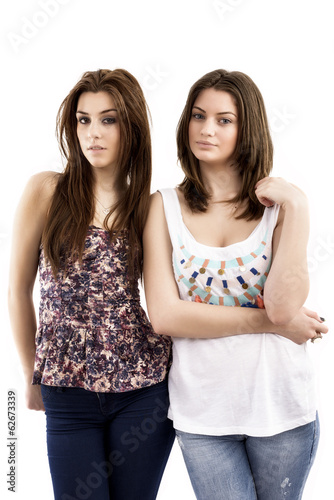 Close-up portrait of two smiling young female friends against wh