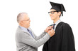 Proud father preparing his son for graduation