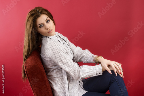 Portrait of a female fashion model posing against red background
