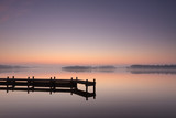 Fototapety Jetty at a lake during a tranquil, foggy dawn.