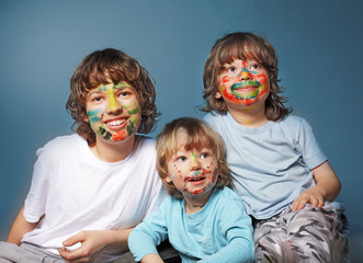 three cheerful brothers with painted faces