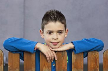 Retrato de niño apoyado en una barandilla de madera