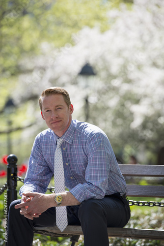 A Businessman In A Shirt With White Tie, Sitting On A Park Bench Under The Shade Of A Tree With Blossom.