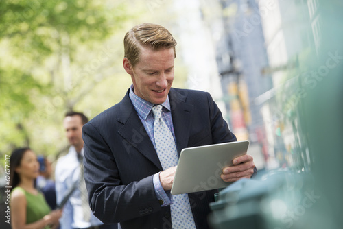 Three Business People Outdoors In The City. A Man Using A Digital Tablet, And A Couple In The Background.