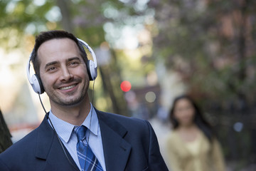 A Man In A Business Suit Wearing White Headphones, Listening To Music.