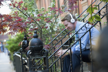 A Man In A Blue Shirt Wearing Headphones And Listening To A Music Player.