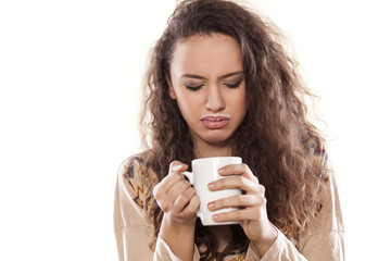 disgusted young girl looking into a cup with milk