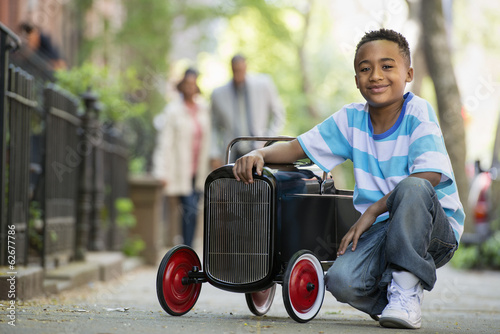 A Young Boy Playing With A Old Fashioned Toy Car On Wheels On A City Street. A Couple Looking On.