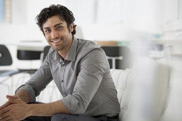 Business. A Man Seated With His Hands Clasped In A Relaxed Pose. Smiling And Leaning Forwards.