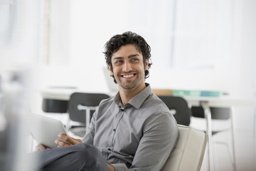 Business. A Man Seated Smiling And Holding A Digital Tablet.