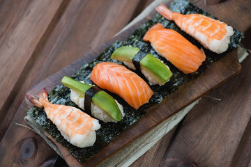Sushi with salmon, shrimp and avocado, rustic wooden background
