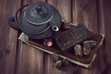 Cast-iron asian teapot and variety of compressed tea
