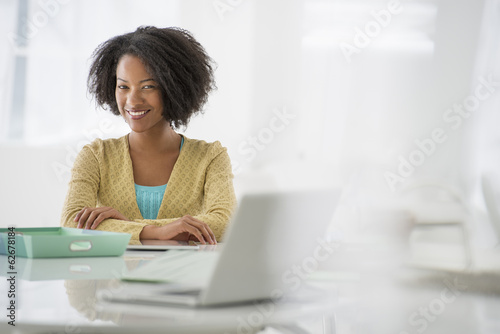Business. A Woman Sitting At A Desk. Digital Tablet And Laptop, And Green Files.