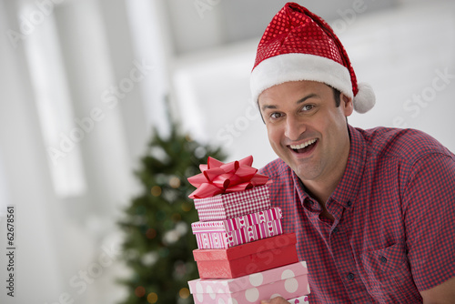 Office Interior. Celebrating Christmas. A Man In A Santa Hat Holding A Stack Of Presents. Decorated Christmas Tree.