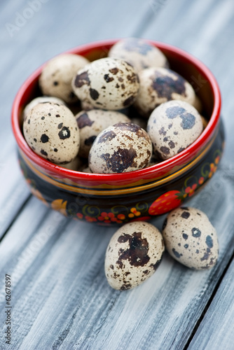 Raw quail eggs in a wooden khokhloma bowl, close-up