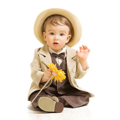 Baby boy well dressed in suit with flower. Vintage children