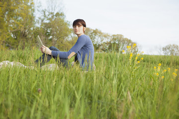 A Young Woman Sitting In An Open Space, A Grass Field, On A Blanket, Holding A Digital Tablet.