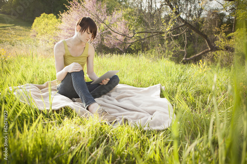 A Young Woman Sitting In A Field, On A Blanket, Reading From A Digital Tablet.