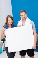 sportliches paar zeigt weißes schild im fitness-studio