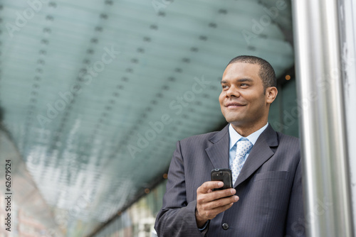 City. A Man In A Business Suit Checking His Messages On His Smart Phone.