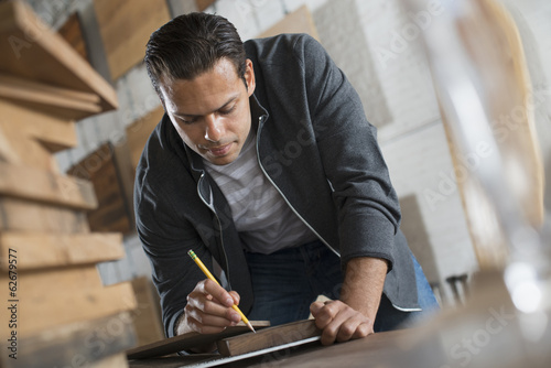 A Young Man In A Workshop Which Uses Recycled And Reclaimed Lumber Using Paper And Pen To Keep Records.