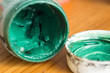 The opened jar with gouache of green color close up