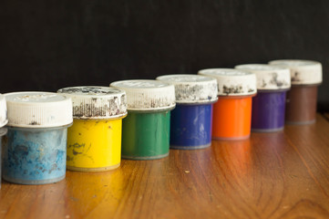 A row from old cans with gouache of different color