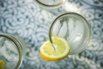 Making Lemonade. Overhead Shot Of Lemonade Glasses With A Fresh Slice Of Lemon In The Edge Of The Glass. Organic Lemonade Drinks.