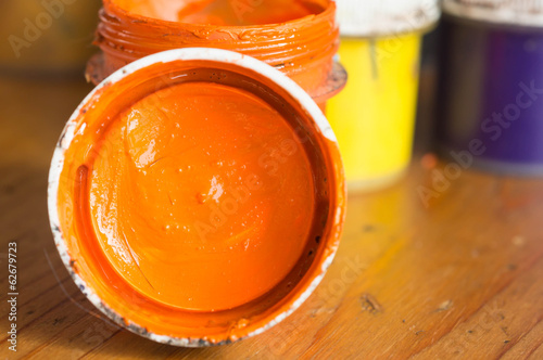Cover and the opened jar with gouache of orange color