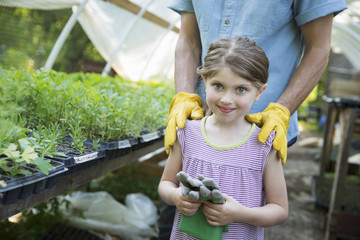 On The Farm. Children And Adults Working Together. A Man And A Young Child With Gardening Gloves, Standing Beside A Bench Of Young Seedling Plants In A Glasshouse.