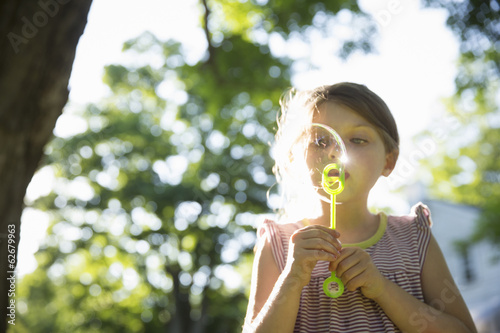 Outdoors In Summer. A Young Girl Blowing Bubbles In The Air Under The Branches Of A Large Tree.
