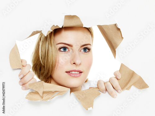 Woman looking through paper hole into the future