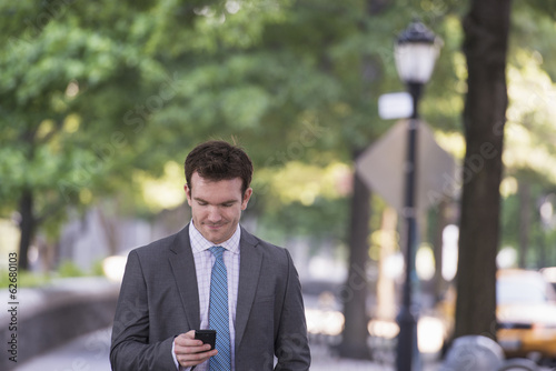 Summer. A Young Man In A Grey Suit And Blue Tie. Using A Smart Phone.