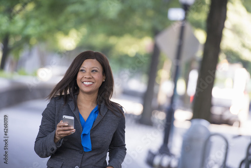 Summer. A Woman In A Grey Suit With A Bright Blue Shirt. Holding A Smart Phone.