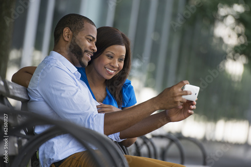 Summer. A Couple Sitting On A Bench, Taking A Selfy Photograph.