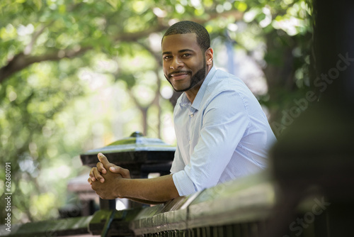 Summer. A Man In A White Shirt Leaning On A Railing.