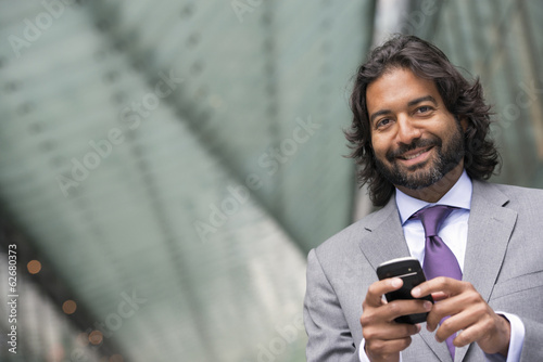 Business People. A Man In A Business Suit With A Full Beard And Curly Hair. Using His Phone.